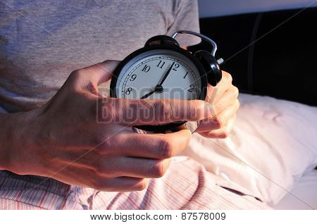 a young caucasian man wearing pajamas in bed setting the alarm clock at 7 before lie down