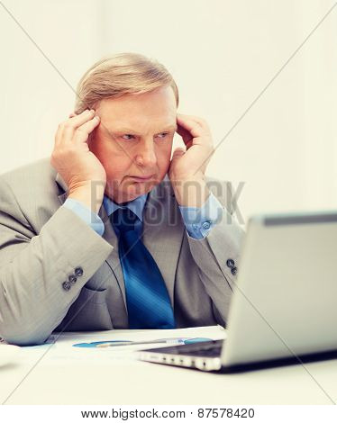 business, technology and office concept - upset older businessman with laptop and charts in office