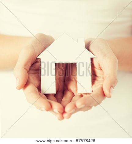 closeup picture of woman hands holding paper house