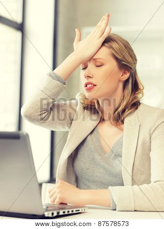indoor picture of businesswoman holding her head with hand
