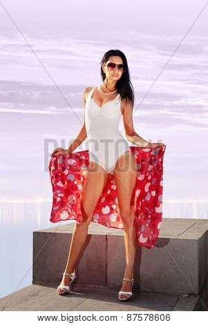 beautiful woman posing in white bathing suit on beach