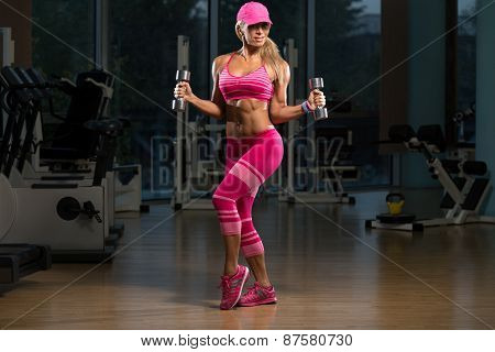 Mature Woman Exercising Biceps With Dumbbells