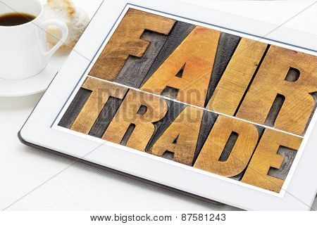 fair trade word abstract typography -  text in letterpress wood type on a digital tablet with a cup of coffee
