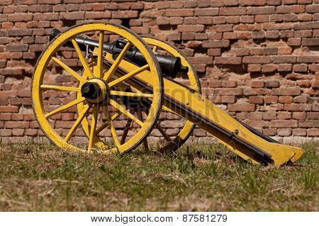 Old cannon in front of a brick wall