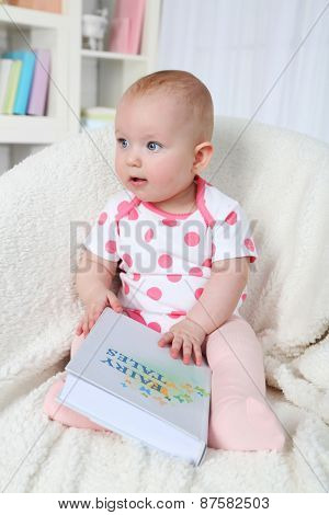 Cute baby girl sitting in arm-chair with book, on home interior background