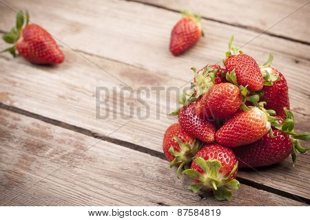 Strawberries on aged wooden background