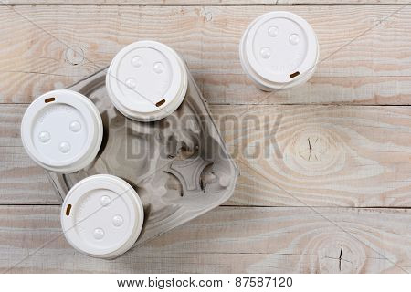 High angle shot of a cardboard take out coffee carrier on a white wood rustic table.Horizontal format with copy space.
