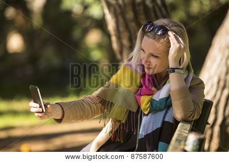 Young woman taking self-portrait through a smartphone while sitting on a park bench.