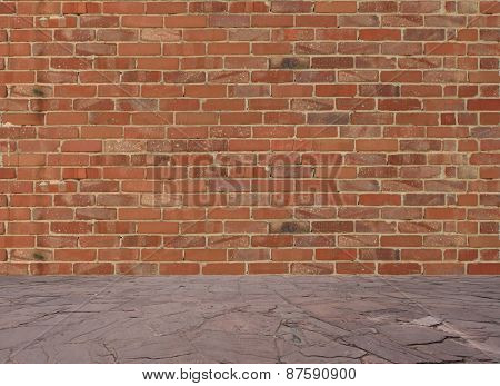 Old red brick wall with stone floor