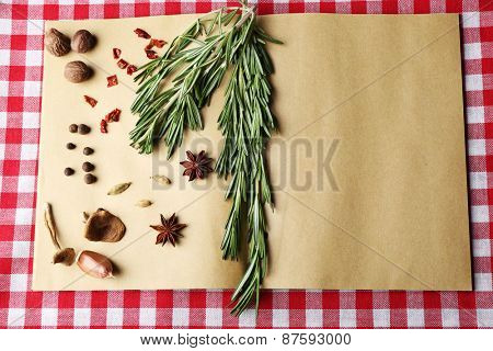 Open recipe book with fresh herbs and spices on tablecloth background
