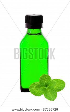 Close Up Of Medicine Bottle With Green Syrup And Mint Herb Isolated On White