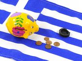 pic of depreciation  - An empty piggy bank on the Greek flag with small euro coins - JPG