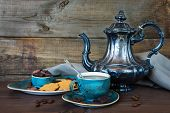 stock photo of pot roast  - Black coffee in blue vintage cup cookies chocolate and antique silver coffee pot on a old dark wooden boards - JPG