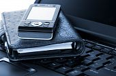 stock photo of mobile-phone  - Organizer and mobile phone laying on laptop - JPG
