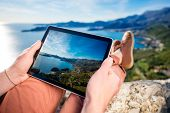 image of sea-scape  - Man holding digital tablet on the mountain top on the sea scape background - JPG