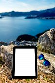 picture of sea-scape  - Digital tablet with empty screen and sunglasses on the rock mountain with sea scape background - JPG