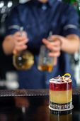 stock photo of bartender  - Vertical shot of a yellow and red cocktail on a bar counter with the blurred view of a bartender behind the counter - JPG