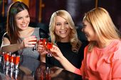 Постер, плакат: Three women have a drink in the bar