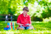 pic of school lunch  - Happy smiling school boy smart student holding a white touch screen tablet computer relaxing on a school yard lawn reading books and having apple for lunch - JPG