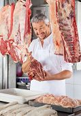 picture of hook  - Happy male butcher holding raw meat with hook in shop - JPG