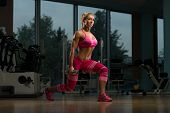 stock photo of squatting  - Middle Age Woman Performing Dumbbell Squats  - JPG