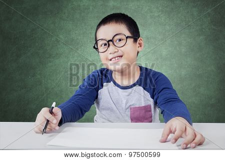 Male Elementary School Student With Paper In Class