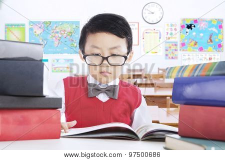 Male Kid Reading Book Lesson In Classroom