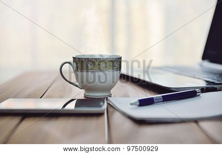 Coffee table with laptop, smartphone and notebook