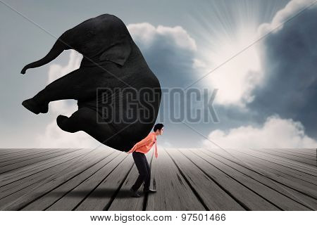Portrait Of Businessman Carrying Heavy Elephant