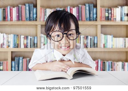 Pretty Child With Glasses And Book In The Library