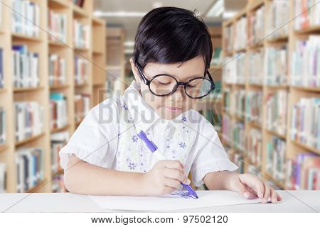 Student Drawing On A Paper In The Library