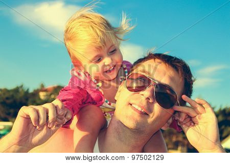 Daughter sat on father's shoulders. A man and a child laughing and holding hands.