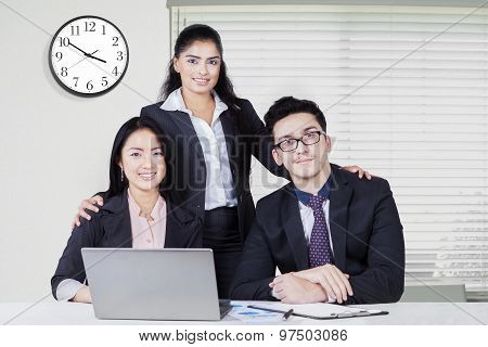 Three Confident Businesspeople At Workplace