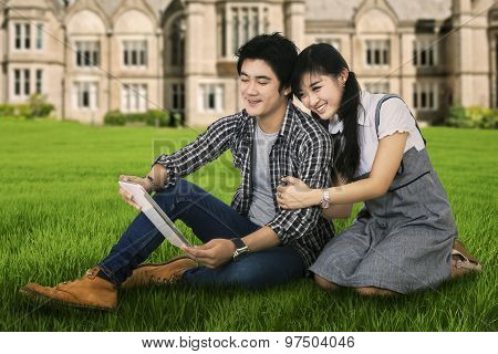 Young Couple Using A Digital Tablet Outdoor