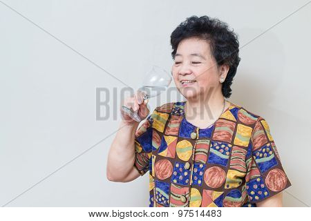 Asian Senior Woman With Glass Of Water, On Reddish Yellow Gray Wall Background
