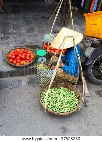 Vietnamese vegetable vendor with baskets