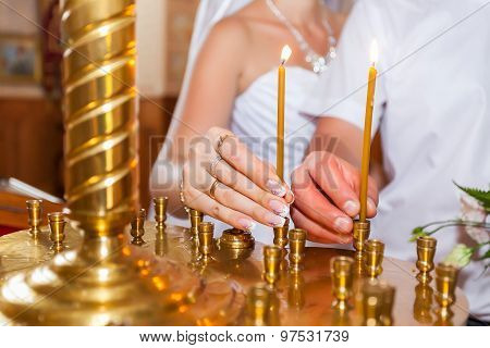 Man And Woman Put A Candle In Church