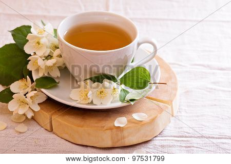 Jasmine tea in a cup with fresh flowers