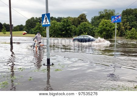 GDANSK, POLAND - July 28: Man cycling and car trying to drive against flood on the street on July 28, 2015 in Gdansk, Poland. Storms and heavy rains hit many parts of Poland and Europe
