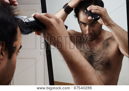 Man Having A Haircut By Himself. Watching In A Mirror