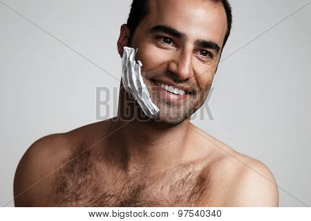 Man With A Shave Foam On A Cheek Is Smiling