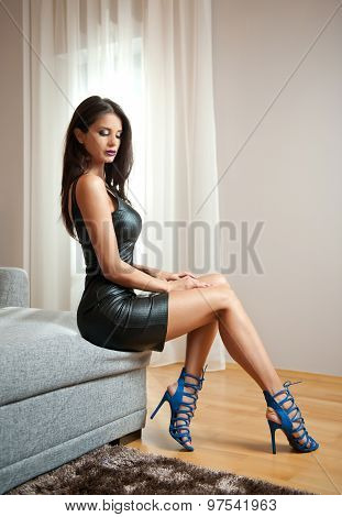 Beautiful sexy brunette young woman wearing black leather short dress sitting on bed