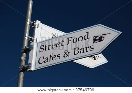 Sign Pointing Towards Street Food, Cafes And Bars
