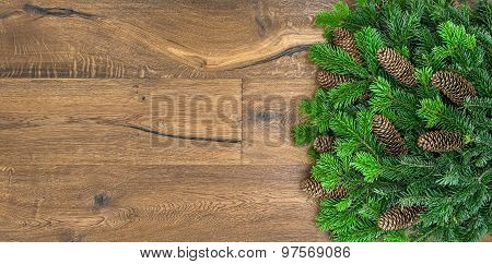 Christmas Tree Branches Over Rustic Wooden Background