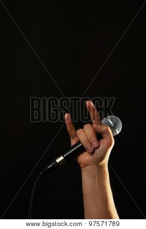Hand With Microphone And Devil Horns Isolated On Black
