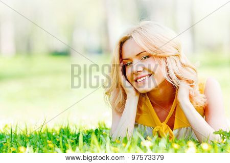 Smilng happy young woman lying on green grass meadow