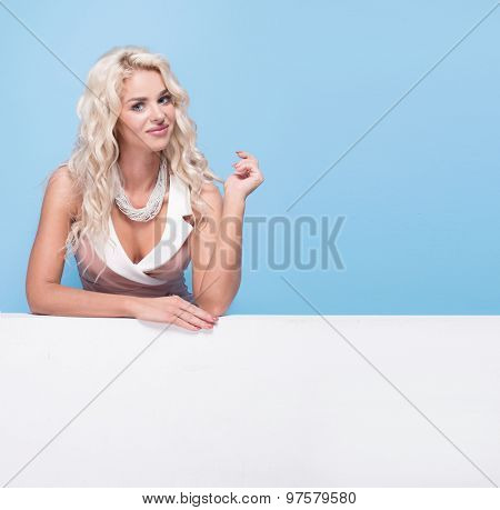 Young blonde smiling woman show blank board on blue