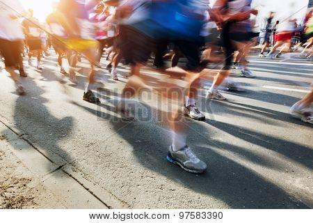 Marathon runners in motion. Running in the city, sun shining.