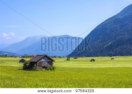 Huts For Storing Materials And Hay On A Green Meadow In The Austrian Alps