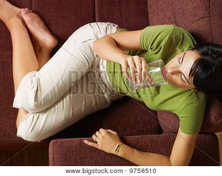 Woman Drinking Water On Sofa